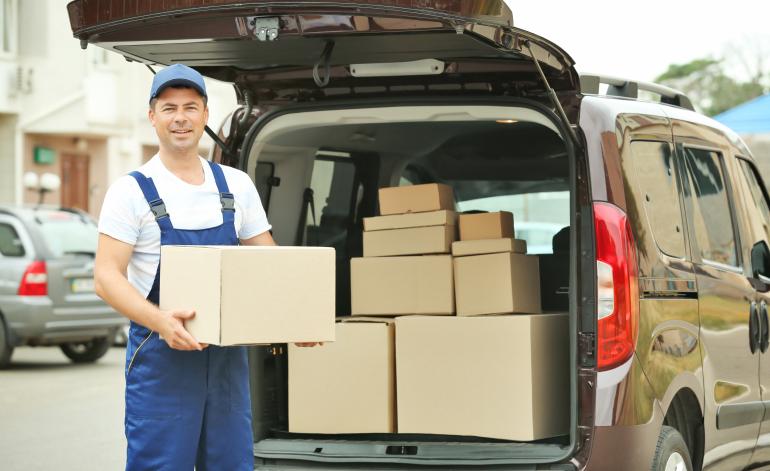 Montaż i transport mebli - pracownik przenosi paczki do auta transportowego